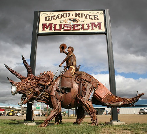 Life-size hybrid metal sculpture of a cowboy riding an iron T-Rex