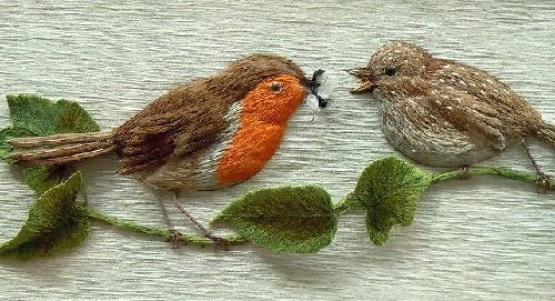 Mother bird feeding its baby with an insect. Stumpwork embroidery by Belgian artist of applied art Christine Paris