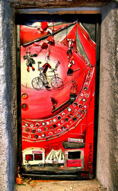 The door with painted on it image seems to be inviting into the world of circus. Valloria, Italy
