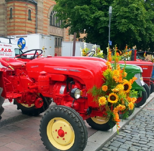 These small cars are used in a parade as a platform for flower arrangements