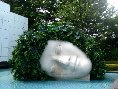 This sculpture of a horizontal head has turned into an artful flower bed