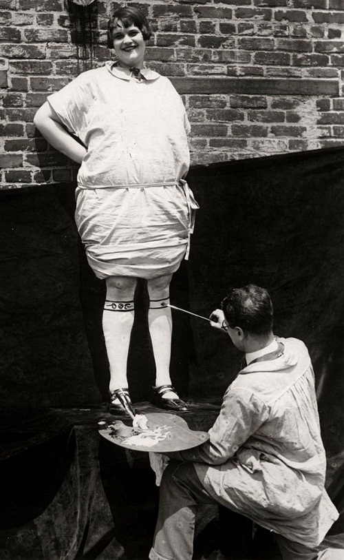 The artist with a palette in his hand paints the legs of a woman. New York, United States of America, retro photo of early XX century, USA