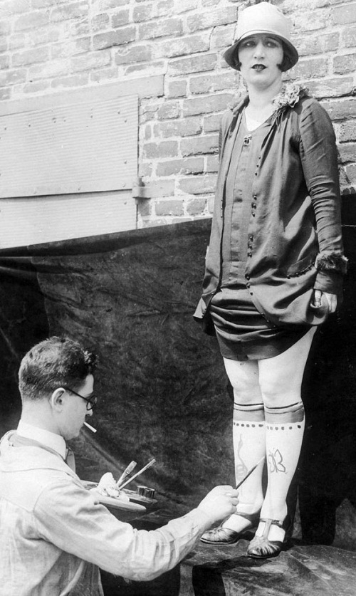The artist with a palette in his hand paints the legs of a woman. New York, United States of America, retro photo of early XX century
