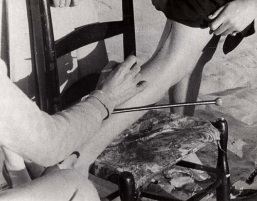 The artist with a brush in his hand paints the legs of a woman. Retro photo of early XX century, USA