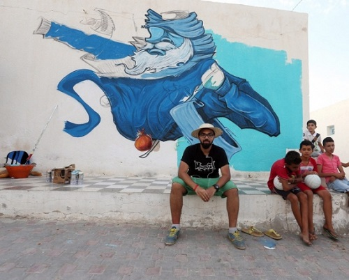 Saudi Arabian street artist Deyaa One sitting in front of his mural. Erriadh village, Tunisia
