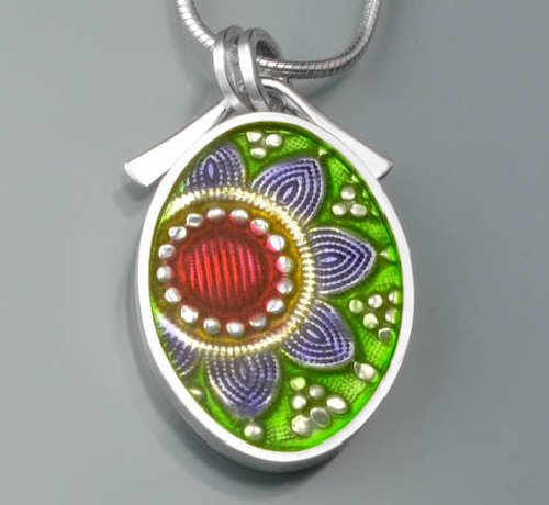 The vintage rose pattern glides into view in this oval shaped pendant