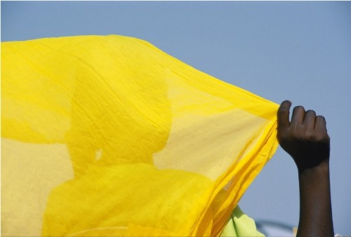 Yellow color. Malian woman with bright scarf on the background of the deep African sky
