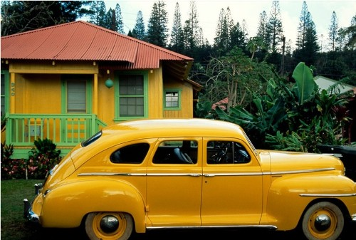 Yellow color. Vintage Plymouth emphasizes the house in the town in Hawaii