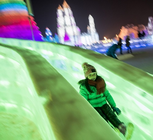 Children slide down colorful icy hills in Harbin, January 5, 2015