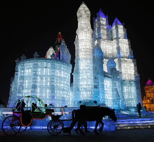 Horse-drawn carriage with tourists drives past ice sculptures in Harbin