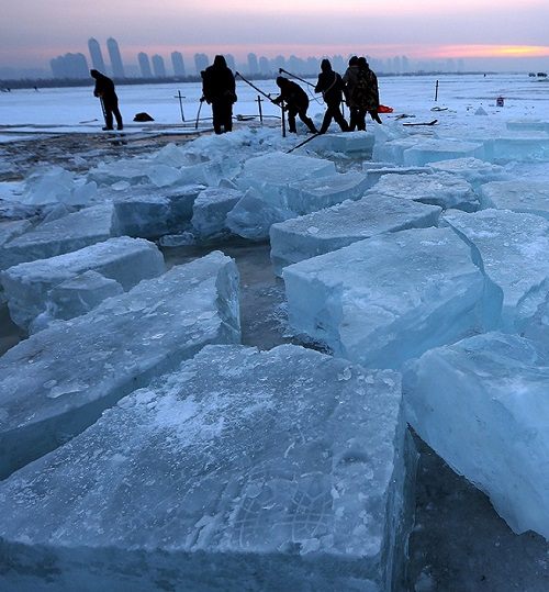 Masters carve ice blocks from the frozen Songhua River