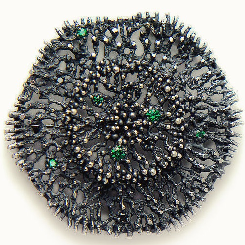 Silver brooch 'Mossy Evening'. The brooch is decorated with emerald and black cubic zirconia high-cut (Swarovski gemstones). Jewelry art by Anna Kiryanova and Ivan Chernykh