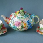Tea pot and two cups decorated with porcelain miniature