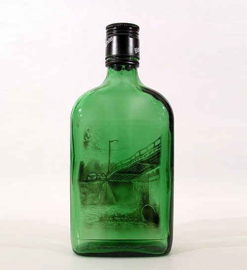 Green bottle with a picture painted with smoke inside it