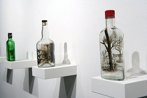 Pictures painted with smoke inside empty glass bottlee. Art by American artist Jim Dingilian