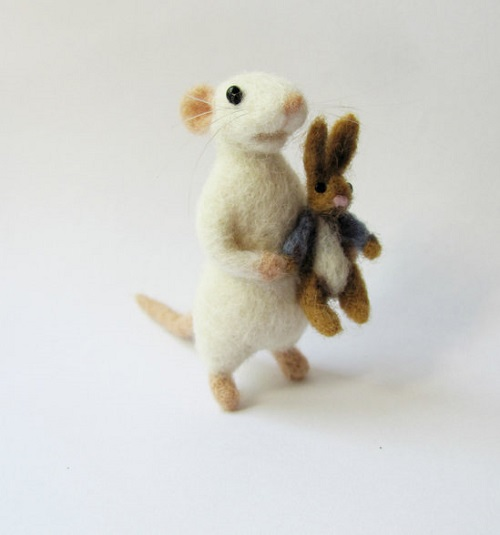 Needle felted mouse holding its Peter the Rabbit toy. Vera Megorskaya felted miniature