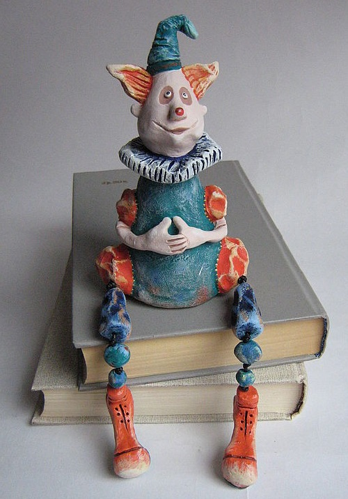 Clown. Made of ceramic mass. Painted with acrylic paints. Feet moving on waxed cord