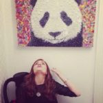 Sarah Connor sitting under her portrait of a panda