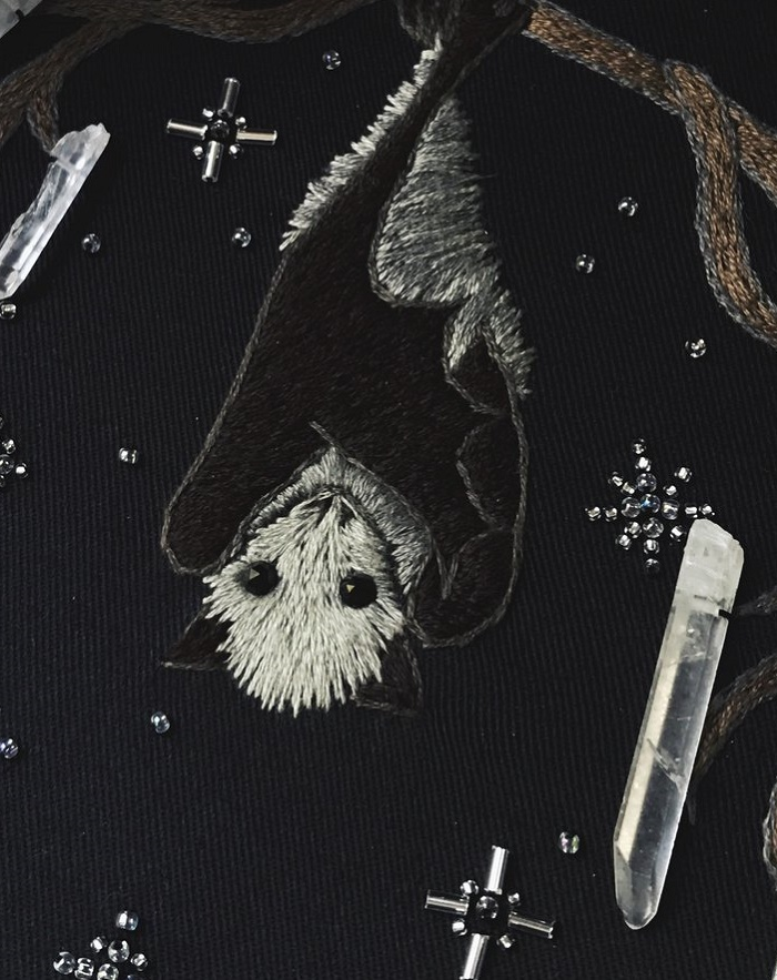 Detail of embroidery with little bat with onyx eyes