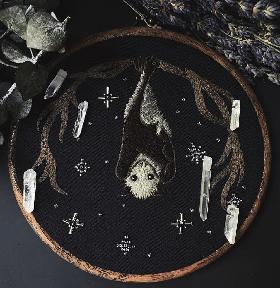little bat with onyxes for eyes, hanging off a branch growing quartz crystals, up against a starry night sky. Lyla Mori spooky symbolic embroideries