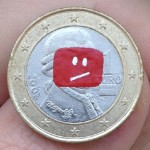 Apu Nahasapeemapetilon of The Simpsons on a Thai coin. YouTube error icon on a Euro coin