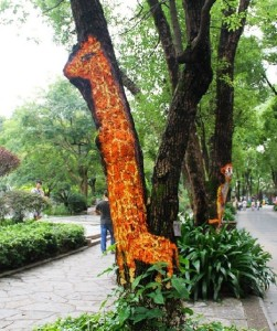 Life-size Giraffe painted on a tree trunk. Creative street art by unknown artists in the city of Guilin