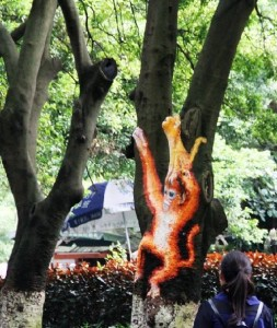 Monkey playing in a tree. Creative street art by unknown artists in the city of Guili