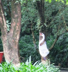 White swan painted on a tree trunk. Chinese street art by unknown artists. Guilin tree art
