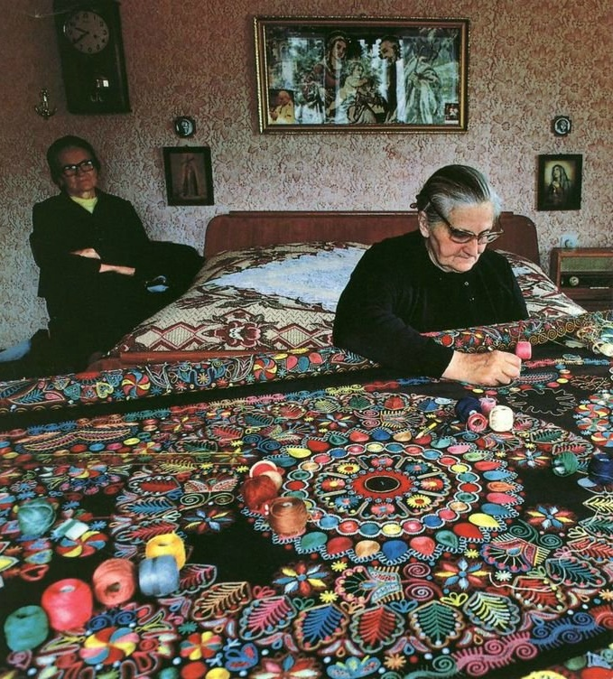 An aged lady emroidering a large carpet