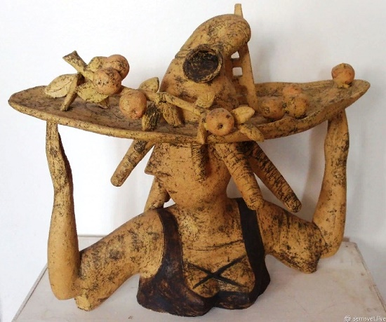 Apple harvesting. Sculpture of a young girl in a hat with folk bagpipes and a still-life of apples on her head. The work done on the motives of the Middle Ages - folk festivals, harvesting, August