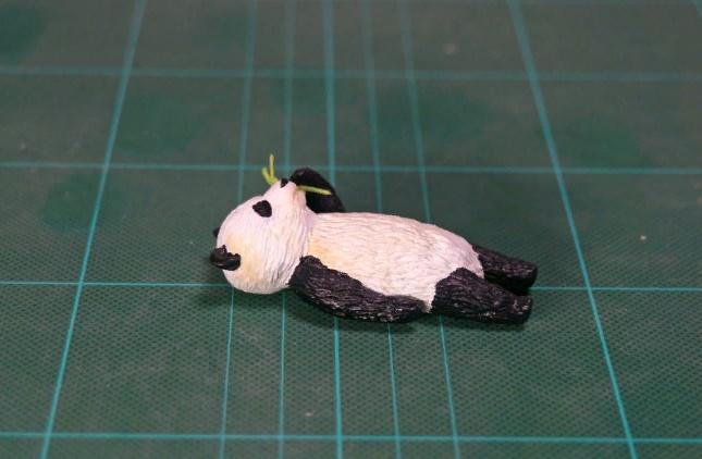 Panda lazily eating grass sculpture