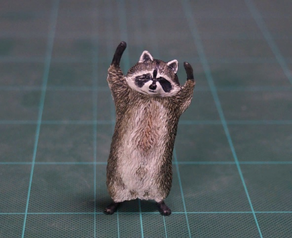 Raccoon hands up sculpture