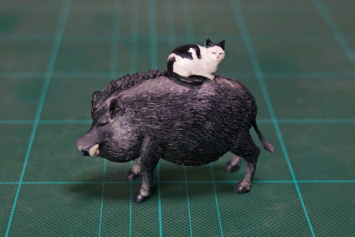 Riding on a pig black and white cat sculpture